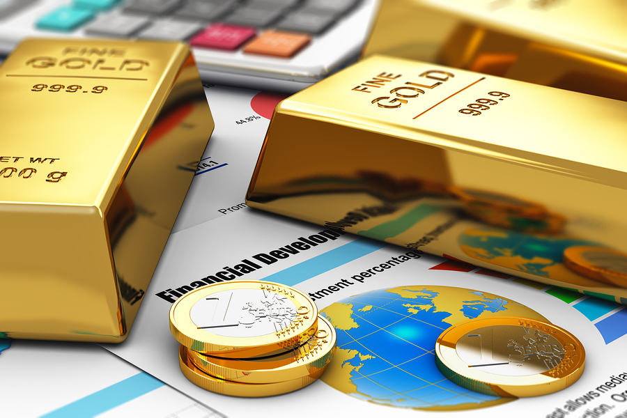 Gold ingots and coins on financial reports